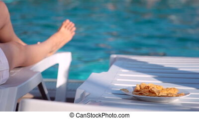 Woman eating potato chips near the swimming pool