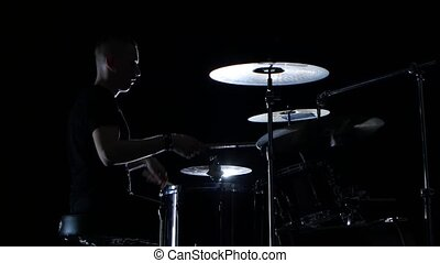 Good music in the performance of a professional drummer. Side view. Black background