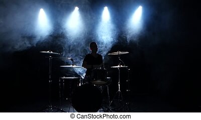 Energetic musician plays good music on drums. Black smoky...