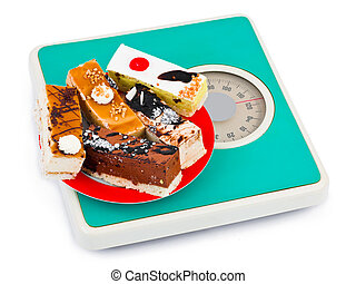 Cakes on weight scale isolated on white background