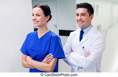 smiling doctor in white coat and nurse at hospital -...