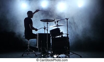 Musician plays professionally good music on drums using...
