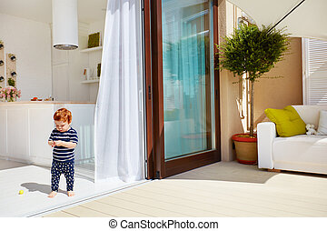 a toddler baby walking on open space kitchen with roof top patio and sliding doors