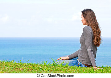 Sad and upset young beautiful woman sitting by the ocean - A...