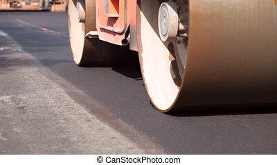 Steamroller compressing asphalt on a new road construction