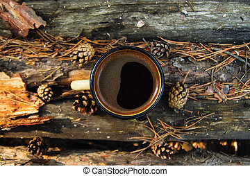 Yellow metal  cup with hot coffee on the wooden background with the coins, needles and bark of tree, top view.