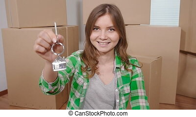 Happy young woman with a key from a new apartment indoors