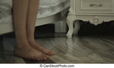 girl wakes up and comes to the bedside table. Feet body...