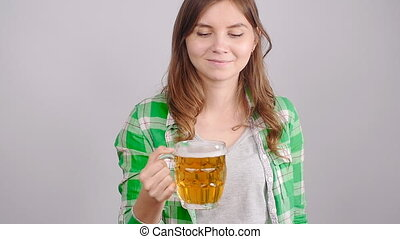 Young woman with a mug of beer indoors