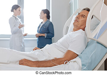 Pleasant middle aged man resting in his bed - I need rest....