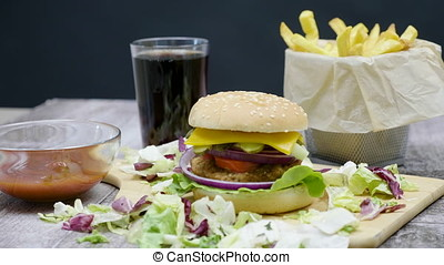 Burger, french fries, cola and ketchup on wooden table over...