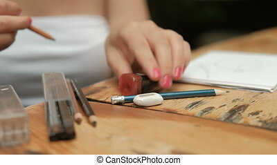 Young woman sharpens pencil and draws sitting at table...