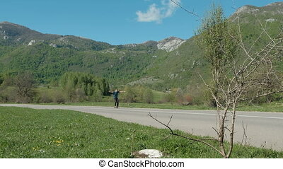 An adult man rides a skateboard among the high mountains.