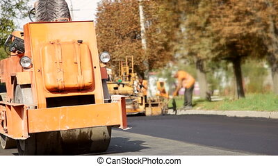 Road Construction - A steamroller rolls and compresses hot...