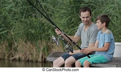 Positive father and son fishing together on pond