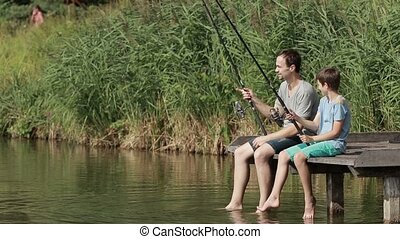 Family fishing with rods by the pond in summer