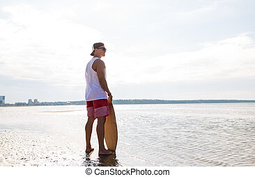 happy young man with skimboard on summer beach -...