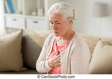 senior woman suffering from heartache at home - old age,...