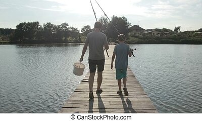 Father and son going fishing with rods on lake - Back view...