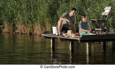 Fishermen having breakfast on wooden pier at pond - Carefree...