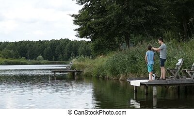 Relaxed father and son fishing at freshwater pond -...
