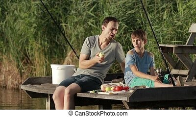 Hipster father and son enjoying picnic by the pond -...