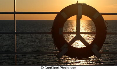 Lifebuoy on a boat crossing the sea at sunset - A boat...