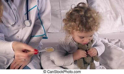 woman doctor giving medicament to kid girl with spoon,...