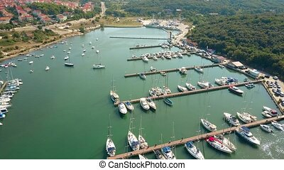 Aerial travelling shot of Mediterranean marina piers and...