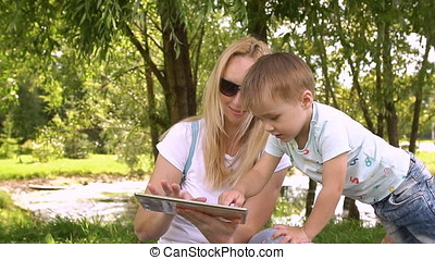 Happy mother and her little son enjoying playing on tablet computer in the park. Slow motion.