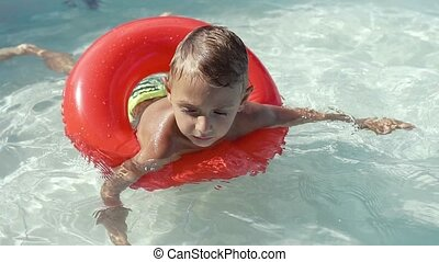 The boy floats on an inflatable pool in the pool