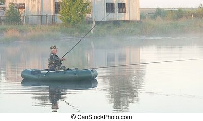 Inflatable boat with a male fisherman on a lake in the fog. Early morning.