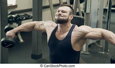 Bodybuilder man trains squat with dumbbells inside gym....