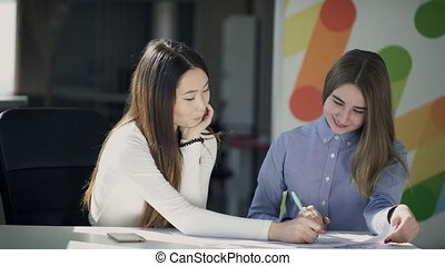 Two young women talk and write sitting at table indoors. -...