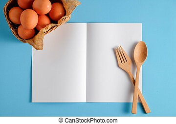 Wooden spoon and white paper on a blue background, for a food menu background.
