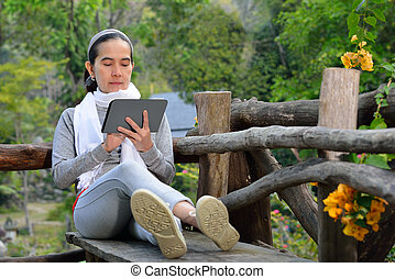 Middle aged woman using tablet computer in the park