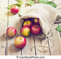Ripe red apples in a bag on wooden background - Ripe red...