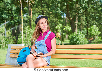 Young beautiful woman reading book at the park - Shot of a...