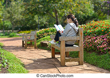 Young woman sitting in the park reading a book