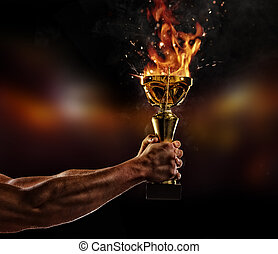 Muscular man arm holding burning trophy cup on black...