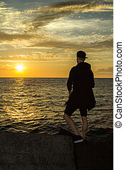 A young man is standing by the sea and looking at the sunset