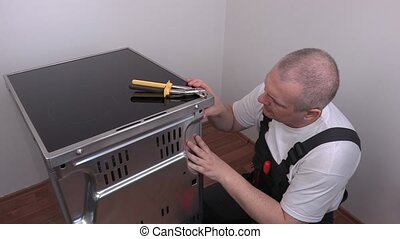 Electrician start fixing rear cover of electric cooker