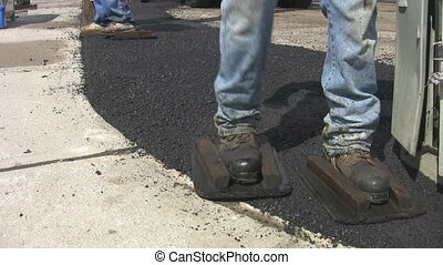 Asphalt boots. 2 shots. - Men wear wooden frames over their...