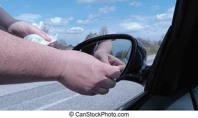 Male cleaning car's mirror on road