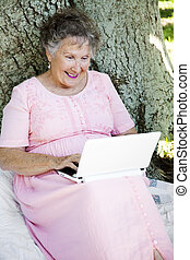 Reading E-mail Outdoors - Senior woman sitting outdoors...