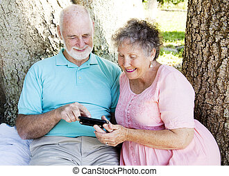 Senior Couple Reads Text Message - Senior couple reading a...