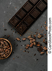 top view of chocolate bar with cocoa beans in bronze bowl