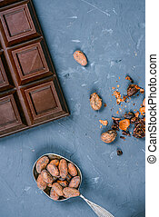 top view of chocolate bar and spoon with cocoa beans
