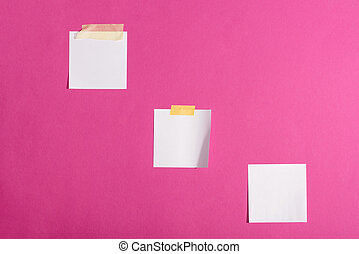 Close-up view of blank white sticky notes isolated on pink