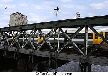 city transport - train and planes passing over a bridge in...